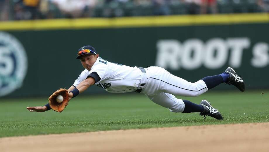 Munenori Kawasaki #61 of the Seattle Mariners dives for a single by Justin Morneau of the Minnesota Twins at Safeco Field on August 19, 2012 in Seattle, Washington. Photo: Otto Greule Jr, Getty Images / 2012 Getty Images