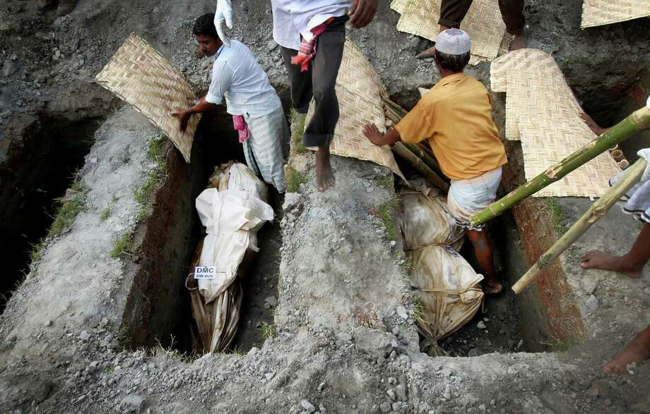 Workers bury unclaimed bodies from the garment factory building collapse in preparation for a mass burial on Wednesday May 1, 2013 in Dhaka, Bangladesh. Several hundred people attended a mass funeral in a Dhaka suburb for 18 unidentified workers who died in the building collapse last week in the country's worst industrial disaster, killing at least 402 people and injuring 2,500. The bodies, rotting in the spring heat, were brought to the graveyard on the back of a flatbed truck. (AP Photo/Wong Maye-E) Photo: Wong Maye-E