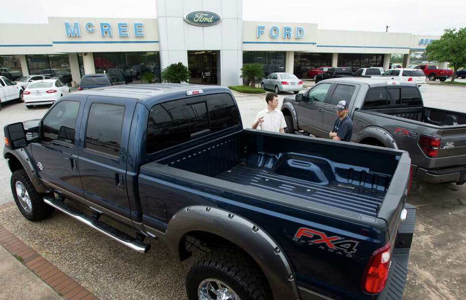 Chris Parks, left, and Tony Lozano look at 2013 F-150 4x4 Supercrews at McRee Ford last month in Dickinson. Sales of F-series trucks in North America were up 24 percent for April. Photo: J. Patric Schneider, Freelance / © 2013 Houston Chronicle