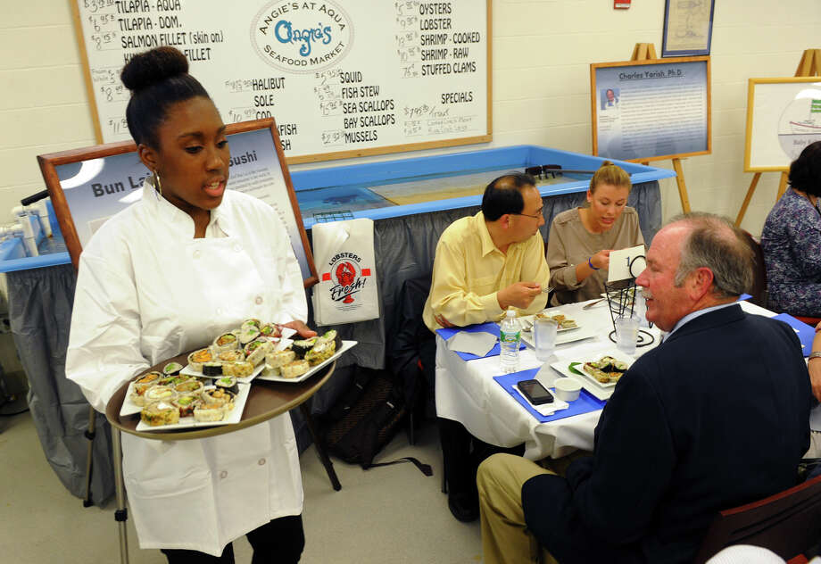 Student Treasen Hooper serves sushi during Bridgeport Regional Aquaculture Science and Technology Education Center's 1st Annual Chef Event at the school in Bridgeport, Conn. on Wednesday May 1, 2013. The event was hosted by Angie's at Aqua Bistro at BRASTEC and featured dishes using sea vegetables, such as sugar kelp and Gracilaria. Chefs Bun Lai, who operates Miya's Sushi in New Haven, and Mark Shadle, who operates G-Zen in Branford, were at the event preparing the dishes for dinner with help from students and guests. Photo: Christian Abraham / Connecticut Post
