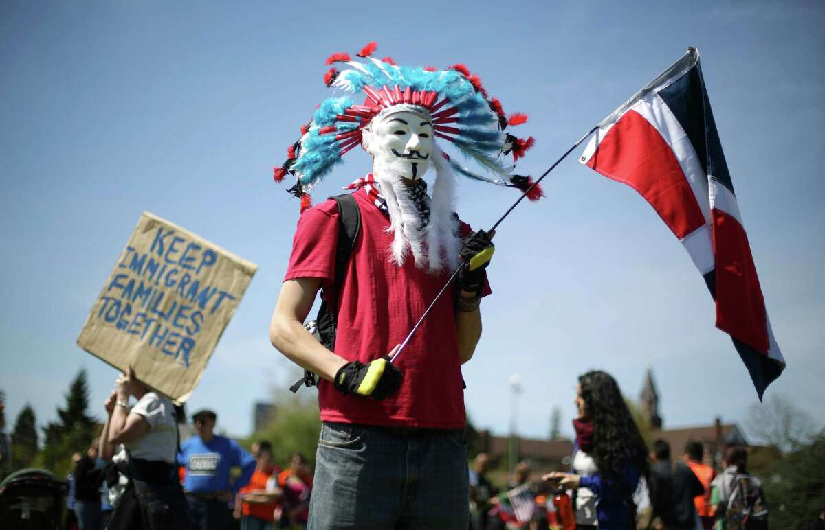 A man who said his name is John Smith holds a Dominican Republic flag during an immigrant rights May Day rally at Judkins Park.