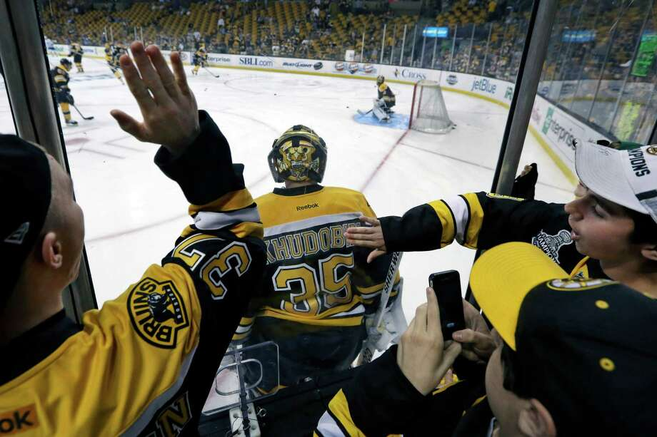 Young fans bang the glass and take photos as Boston Bruins goalie Anton Khudobin (35) skates by during warmups before Game 1 against the Toronto Maple Leafs in a first-round NHL hockey playoff series in Boston, Wednesday, May 1, 2013. Photo: Elise Amendola