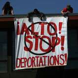 People unfurl a banner during an immigrant rights May Day march.