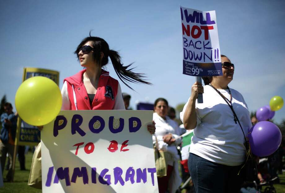 Emily Rodriguez, 15, left, from Mexico, holds a sign during an immigrant rights May Day rally and march. Photo: JOSHUA TRUJILLO, SEATTLEPI.COM / SEATTLEPI.COM