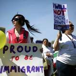 Emily Rodriguez, 15, left, from Mexico, holds a sign during an immigrant rights May Day rally and march.