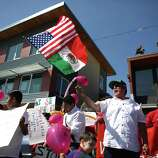 People gather outside Casa Latina during an immigrant rights May Day rally and march.