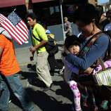 Marchers, including Lorena Sanchez and her daughter Zoe make their way through the International District.