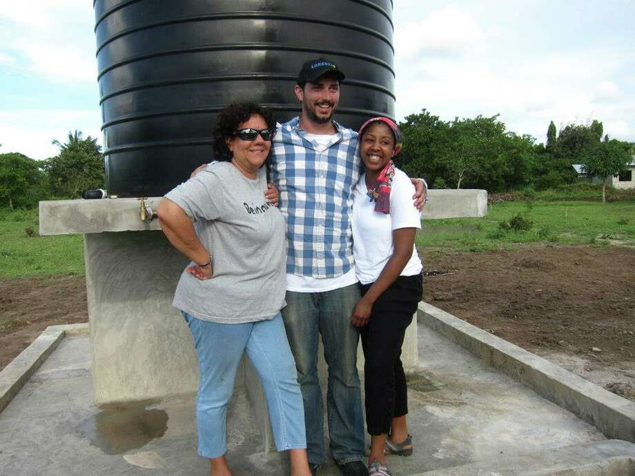 African Reflections Foundation founder Maria Pool (left) poses in front of a newly-installed solar powered well in Tanzania, Africa, with The Sky is Not Limited founders Kevin Bailey and his wife, Tiffany. (Kevin Bailey)