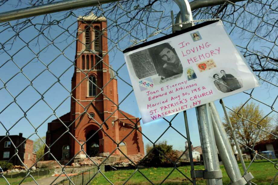 A memorial to a couple wedded at the church hangs on the fence surrounding St. Patrick's Roman Catholic Church on Wednesday, May 1, 2013, in Watervliet, N.Y. The signs says Joan E. Tierney and Edward W. Atkinson were married at the church on Aug. 30, 1952. (Cindy Schultz / Times Union) Photo: Cindy Schultz / 10022220A
