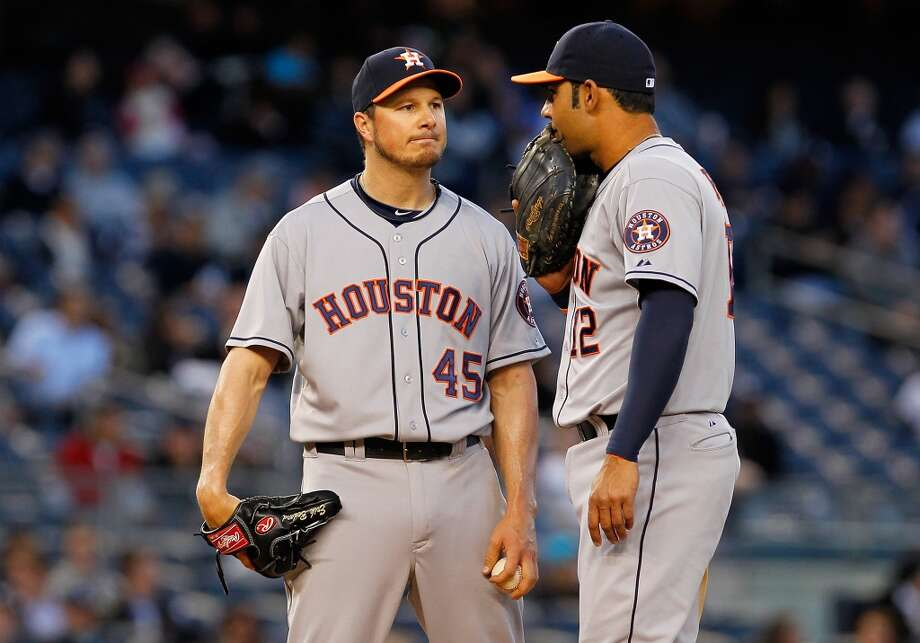 Erik Bedard #45 of the Astros and teammate Carlos Pena #12 meet on the mound against the Yankees.