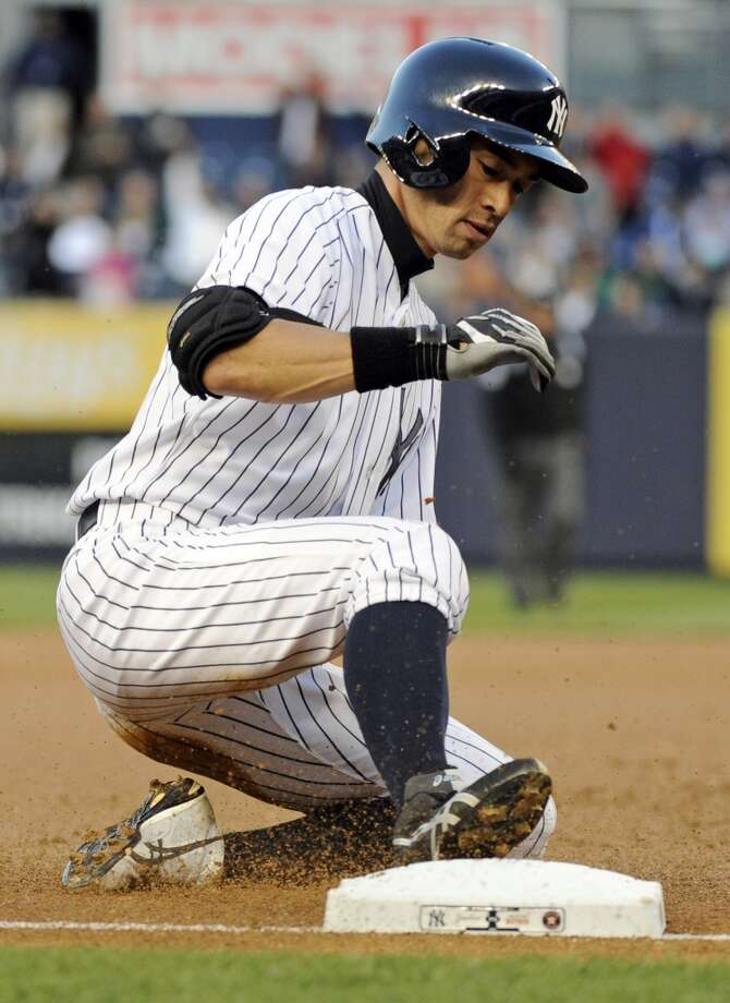 Ichiro Suzuki slides into third base with a triple.