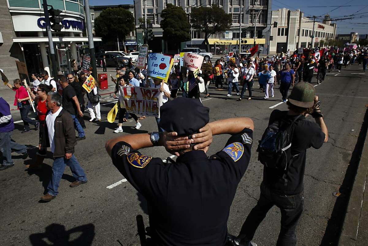 A San Francisco Police officer covers his ears as the public address speakers pass by and the chanting got too loud on Van Ness Avenue. Hundreds of supporters of immigration rights marched to the Civic Center Plaza in San Francisco, Calif., for a rally on Wednesday, May 1, 2013.