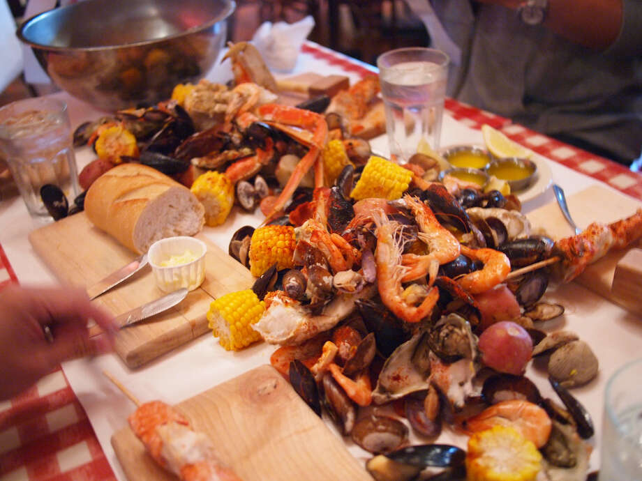 The Crab Pot's ''Seafeast'': Hammer and bib ready? No need for plates or forks when the bucket of food known as the ''Seafeast'' (pictured) is sprawled out onto a butcher-paper-lined table. ''The Alaskan'' Seafeast is  $38.95 per person. At Pier 57, 1301 Alaskan Way. Photo: othree, Flickr. Photo: Http://www.flickr.com/photos/othree/5933228919/in/photostream/