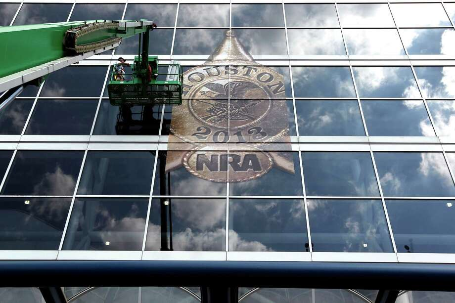 The National Rifle Association's 142 Annual Meetings and Exhibits logo is placed on the George R. Brown Convention Center by Lynn Creel, left, and Don Reynolds with Display Graphics Wednesday, May 1, 2013, in Houston. 