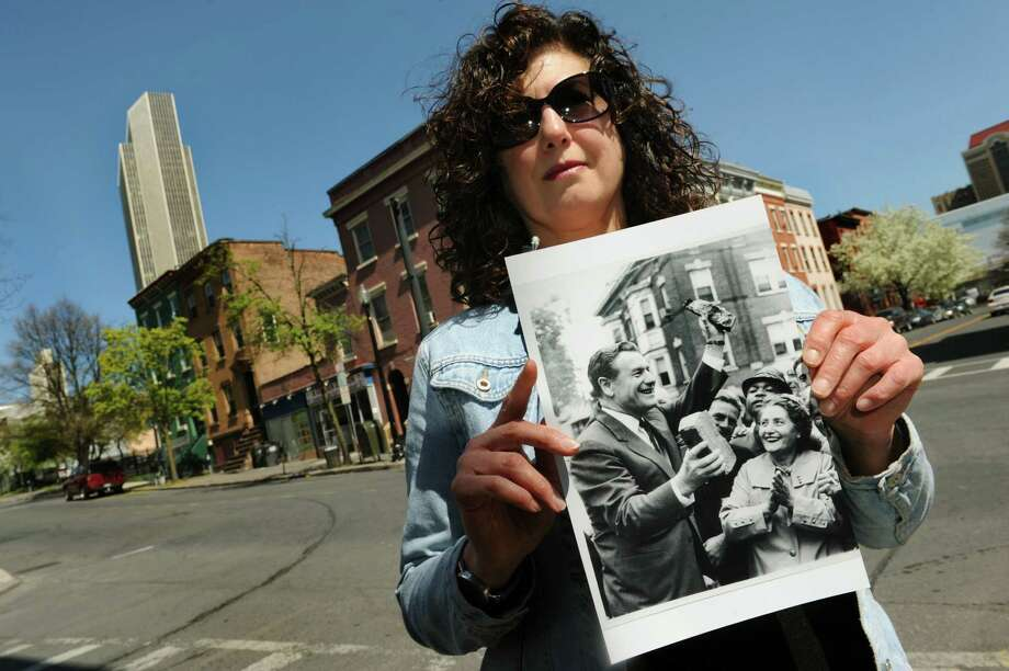 "Mary Paley of Albany holds an historic photograph on the corner of Madison Avenue and Grand Street on Wednesday, May 1, 2013, in Albany, N.Y. The photo is of Nelson Rockefeller at the time when an Italian neighborhood was demolished to make way for the Empire State Plaza. Paley is making a documentary entitled ""The Neighborhood That Disappeared."" (Cindy Schultz / Times Union) Photo: Cindy Schultz / 10022236A"