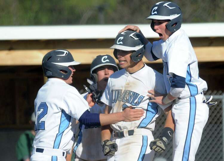 Columbia's Ryan Puentes, center, is congratulated after hitting a grand slam during their boy's high