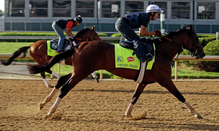 Exercise rider Javier Harrera rides Kentucky Derby hopeful Normandy Invasion, right, in front Goldencents during a workout at Churchill Downs Wednesday, May 1, 2013, in Louisville, Ky. (AP Photo/Morry Gash) Photo: Morry Gash