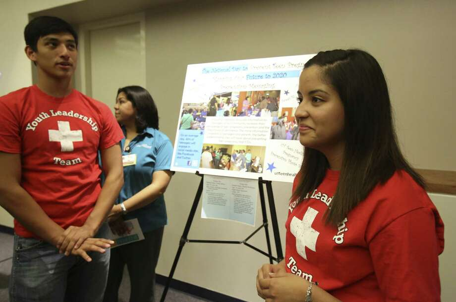Thomas Rodriguez, 16, and Elisha Jeffries, 16, speak about their poster as part of Metro Health's Project WORTH program during the National Day to Prevent Teen Pregnancy. Photo: Helen L. Montoya / San Antonio Express-News