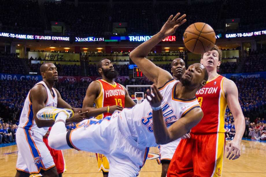 Thunder small forward Kevin Durant falls while trying to take a rebound away from Rockets center Omer Asik. Photo: Smiley N. Pool, Houston Chronicle