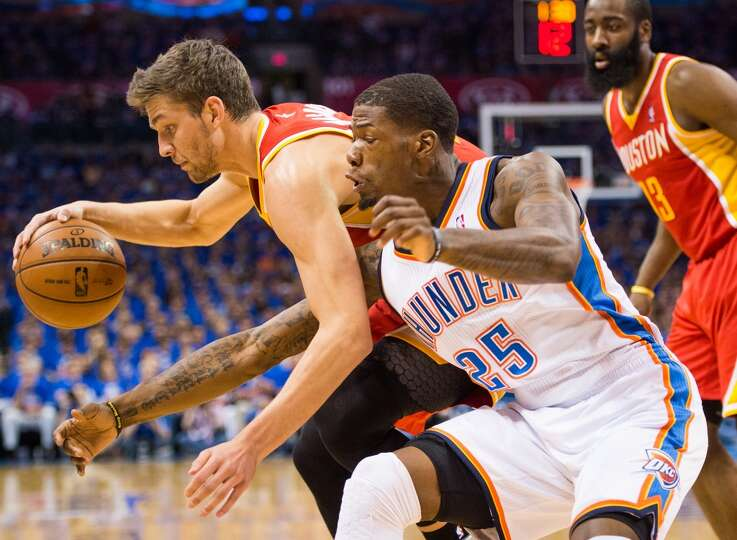 Thunder guard DeAndre Liggins reaches in to try and steal the ball from Rockets forward Chandler Par