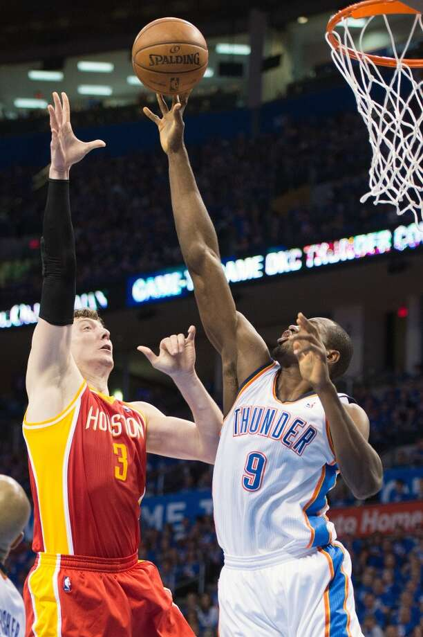 Thunder power forward Serge Ibaka blocks a shot by Rockets center Omer Asik. Photo: Smiley N. Pool, Houston Chronicle