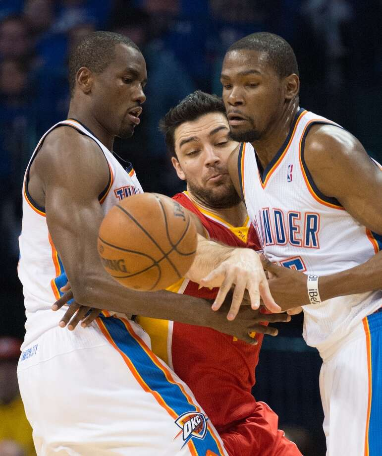 Rockets shooting guard Carlos Delfino knocks the ball away from Thunder small forward Kevin Durant as he fights the pick from power forward Serge Ibaka. Photo: Smiley N. Pool, Houston Chronicle