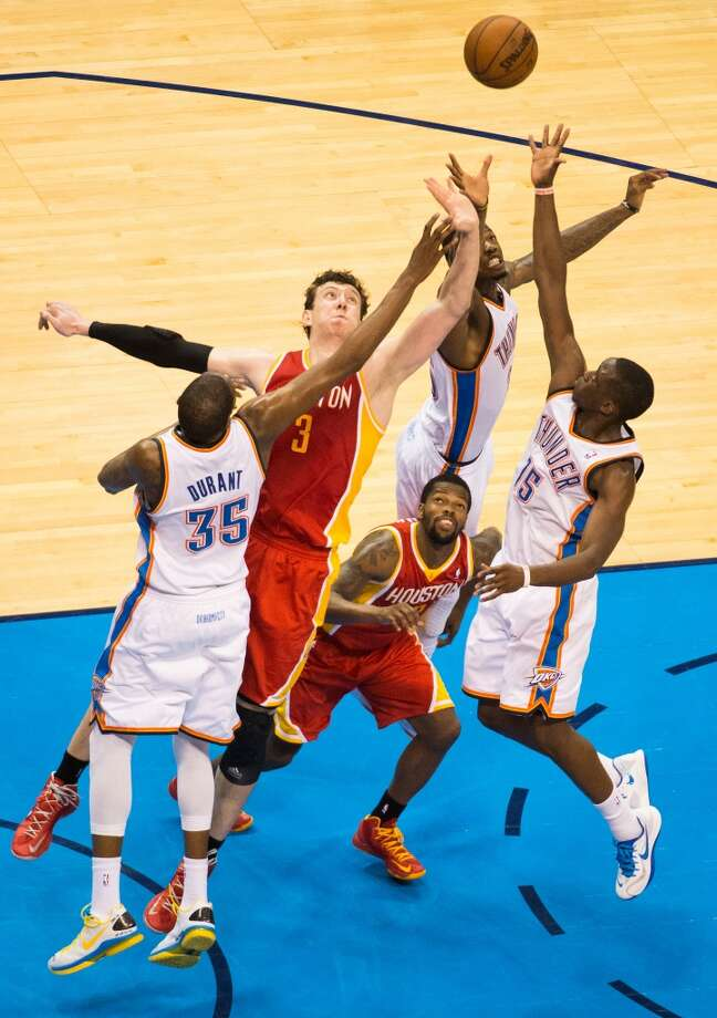 Rockets center Omer Asik and guard Aaron Brooks fight for a rebound with the Thunder's Kevin Durant, DeAndre Liggins and Reggie Jackson. Photo: Smiley N. Pool, Houston Chronicle