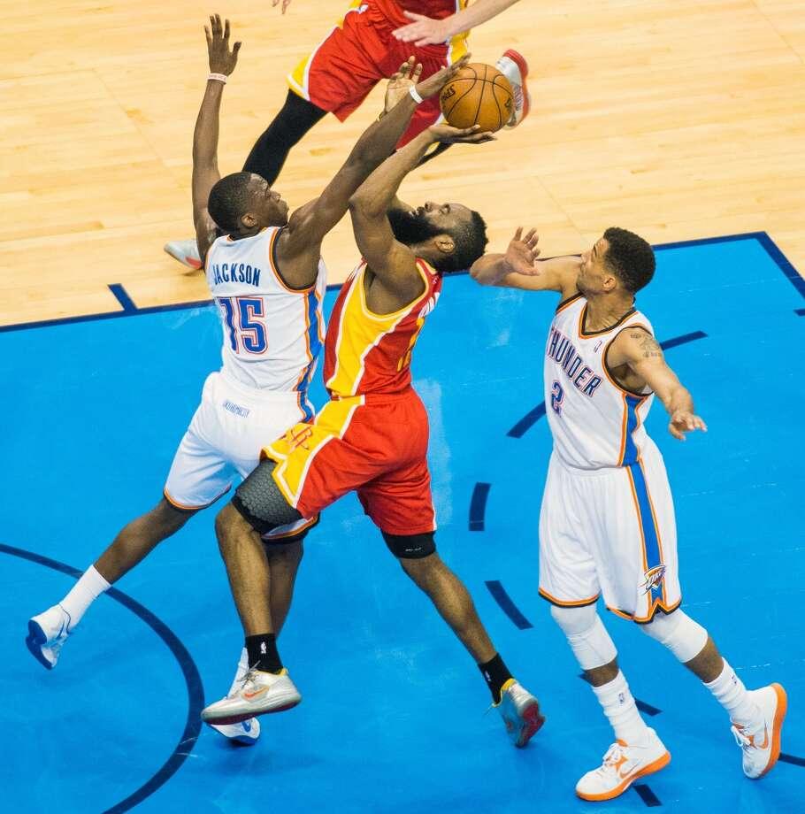 Rockets guard James Harden drives between Reggie Jackson and Thabo Sefolosha. Photo: Smiley N. Pool, Houston Chronicle