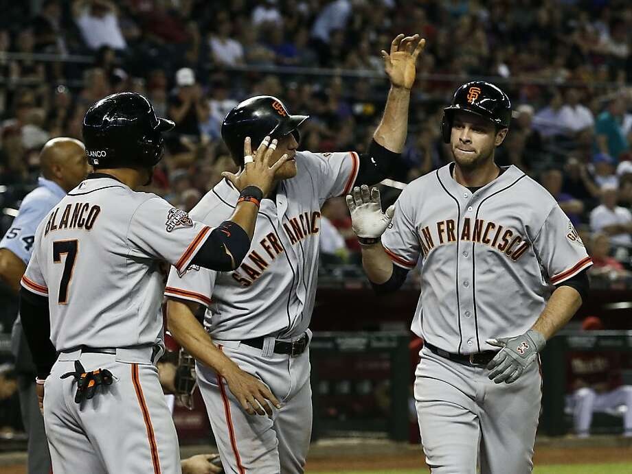 San Francisco Giants' Brandon Belt, right, celebrates his 3-run home run against the Arizona Diamondbacks with teammates Gregor Blanco (7) and Hunter Pence during the eighth inning of a baseball game, on Wednesday, May 1, 2013, in Phoenix. (AP Photo/Ross D. Franklin) Photo: Ross D. Franklin, Associated Press