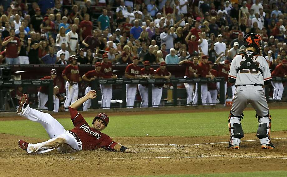 Arizona Diamondbacks' Eric Chavez scores a run as San Francisco Giants' Buster Posey catches a late throw into home plate during the sixth inning of a baseball game, on Wednesday, May 1, 2013, in Phoenix. (AP Photo/Ross D. Franklin) Photo: Ross D. Franklin, Associated Press