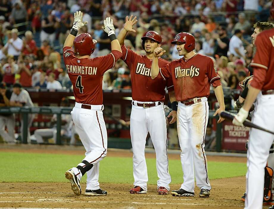 PHOENIX, AZ - MAY 01:  Cliff Pennington #4 of the Arizona Diamondbacks celebrates with teammates Eric Chavez #12 and AJ Pollock #11 after hitting a three-run home run in the second inning against Tim Lincecum #55 of the San Francisco Giants at Chase Field on May 1, 2013 in Phoenix, Arizona.  (Photo by Norm Hall/Getty Images) Photo: Norm Hall, Getty Images