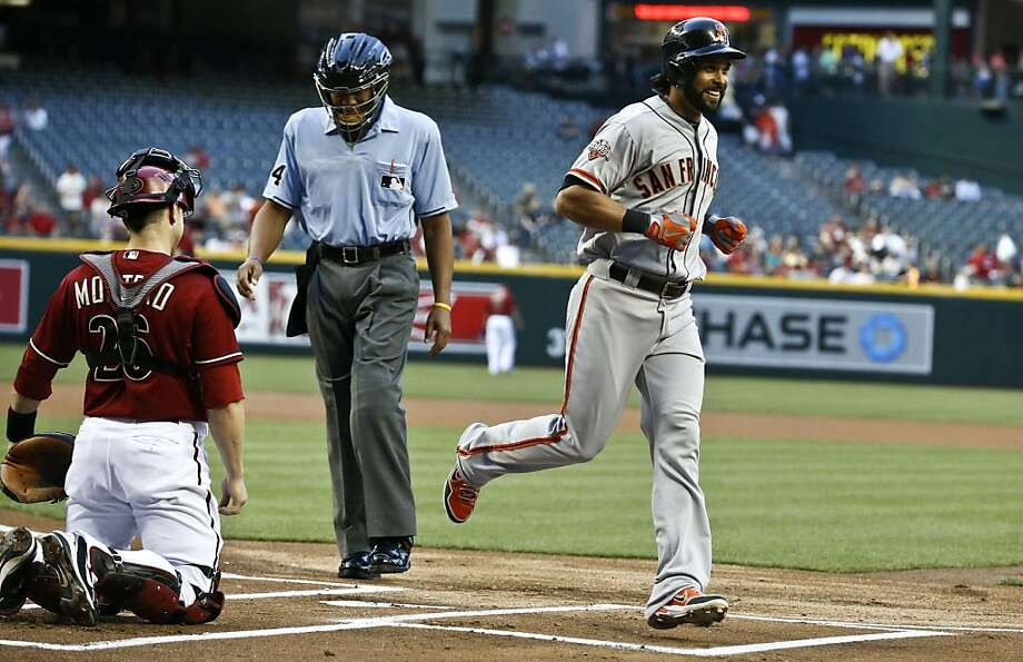 San Francisco Giants' Angel Pagan, right, crosses home plate after hitting a home run as Arizona Diamondbacks' Miguel Montero, left, looks on and umpire C.B. Bucknor checks that home plate was touched during the first inning of a baseball game on Wednesday, May 1, 2013, in Phoenix. (AP Photo/Ross D. Franklin) Photo: Ross D. Franklin, Associated Press