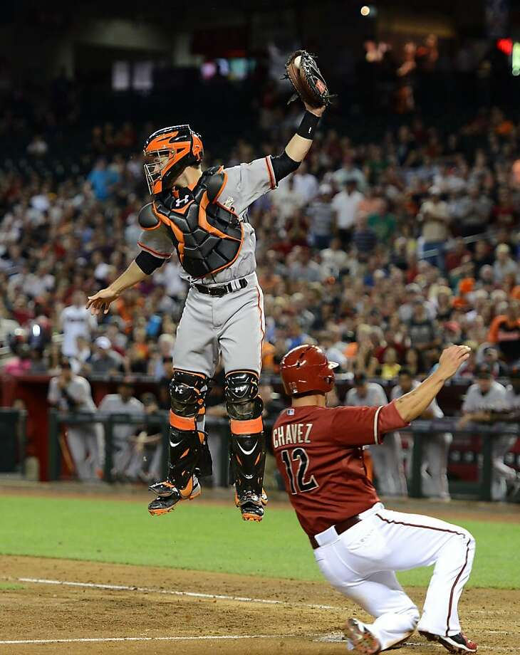PHOENIX, AZ - MAY 01:  Buster Posey #28 of the San Francisco Giants jumps to make a catch on a throw from the outfield as Eric Chavez #12 of the Arizona Diamondbacks slides into home plate safely at Chase Field on May 1, 2013 in Phoenix, Arizona.  (Photo by Norm Hall/Getty Images) Photo: Norm Hall, Getty Images