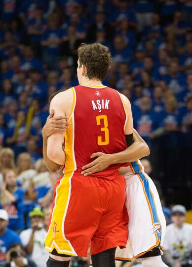 Rockets center Omer Asik is wrapped up by Thunder shooting guard Thabo Sefolosha for a foul as the t