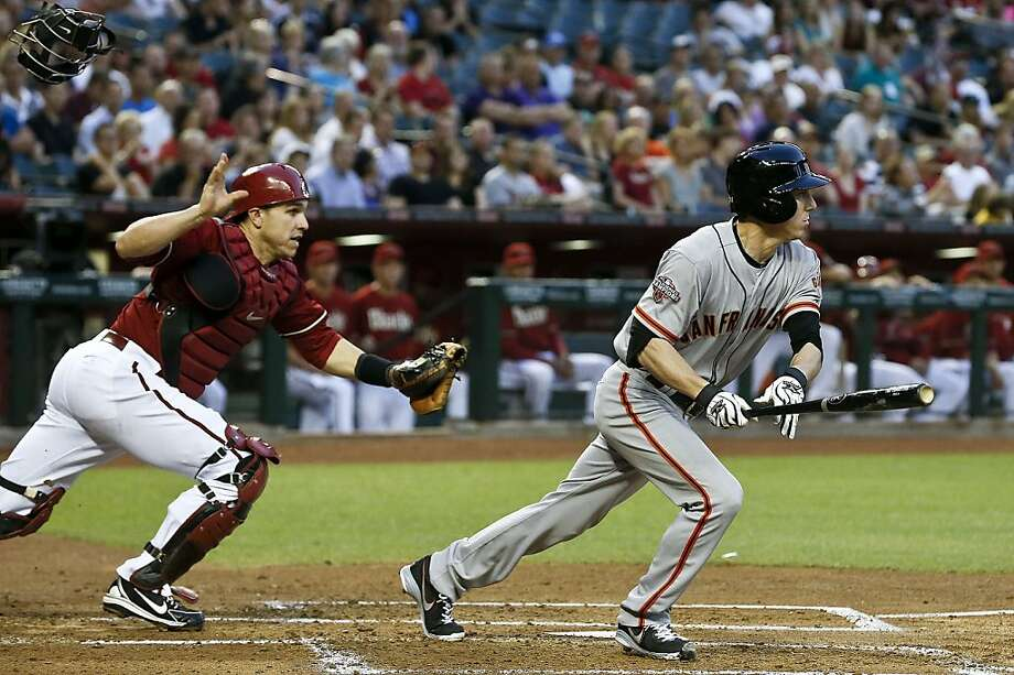 Arizona Diamondbacks' Miguel Montero, left, runs after a swinging bunt hit by San Francisco Giants' Tim Lincecum during the second inning of a baseball game, on Wednesday, May 1, 2013, in Phoenix. (AP Photo/Ross D. Franklin) Photo: Ross D. Franklin, Associated Press
