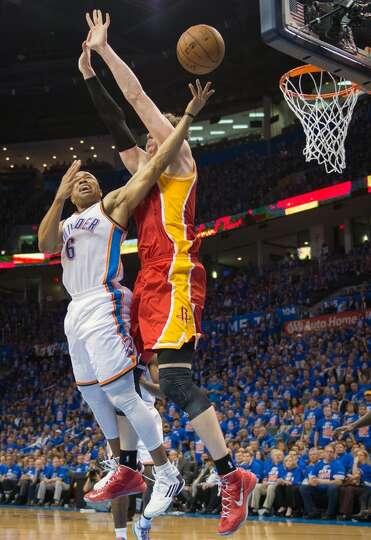 Rockets center Omer Asik knocks the ball away from Thunder point guard Derek Fisher.