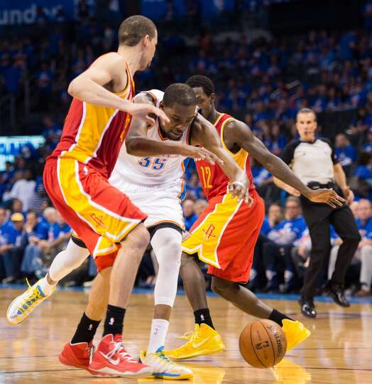 Thunder small forward Kevin Durant loses the ball as he tries to drive between Rockets shooting guar