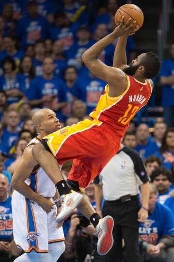 Rockets guard James Harden shoots over Thunder point guard Derek Fisher.