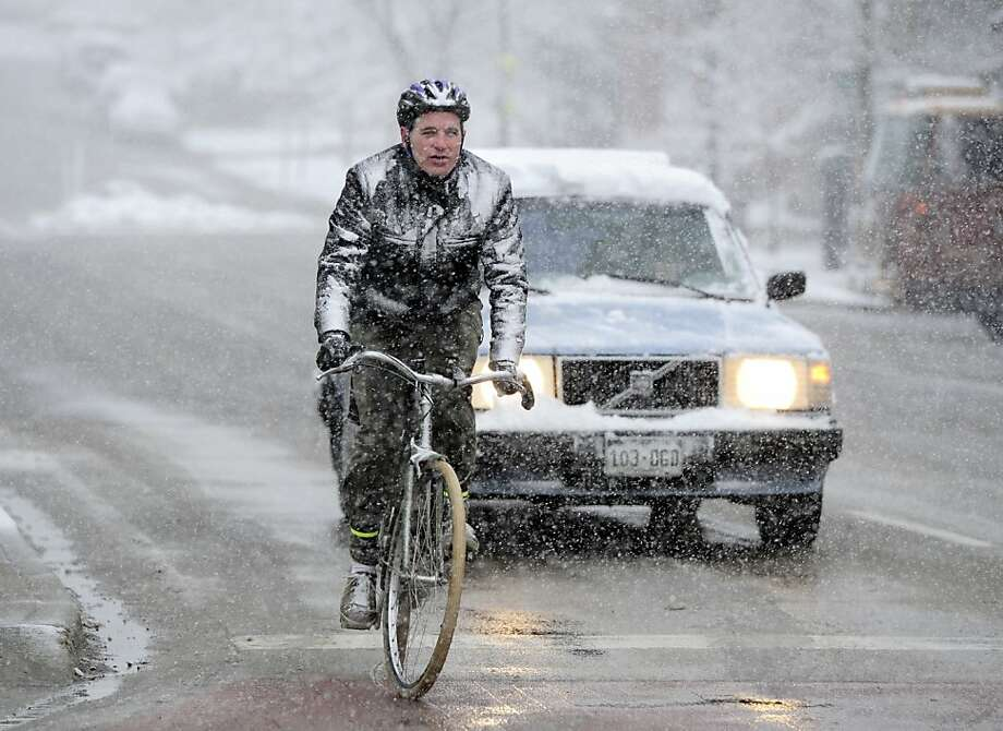 Dan Hopkins, rides his way to work  during the Wednesday morning snow in Boulder, Colorado on May 1, 2013. After a warm weekend snow is falling in Colorado.  (AP Photo/The Daily Camera, Paul Aiken) NO SALES Photo: Paul Aiken, Associated Press