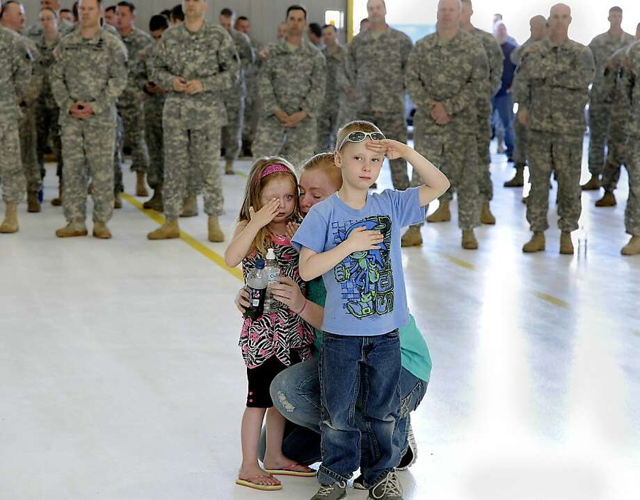 C.J. Richards, 6, salutes while his aunt, Sgt. Ashley Corey, prepares for deployment to Afghanistan as the Michigan Army National Guard Charlie Company 3/238th General Support Aviation Battalion leaves Grand Ledge, Mich. on Wednesday, May 1, 2013. Corey's mother, Della Corey, comforts Aaryon Johnson, 3, a niece of Sgt. Corey. (AP Photo/The State Journal, Rod Sanford) Photo: Rod Sanford, Associated Press