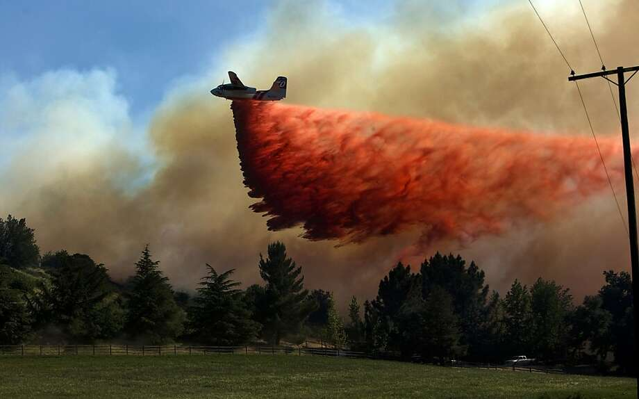 An airplane drops fire retardant near a home as firefighters battle a wildfire on Federal Indian Reservation land west of Banning, California, where the blaze consumed more than 1,500 acres and destroyed several homes on Wednesday, May 1, 2013. (Gina Ferazzi/Los Angeles Times/MCT) Photo: Gina Ferazzi, McClatchy-Tribune News Service