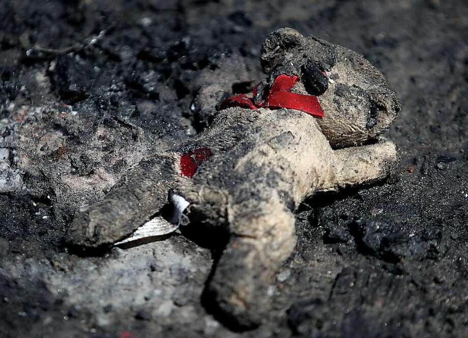 A burnt teddy bear sits  in ash and debris outside of the destroyed apartment building in Jerome, Idaho on Wednesday, May 1 2013. (AP Photo/Times-News, Ashley Smith) Photo: Ashley Smith, Associated Press