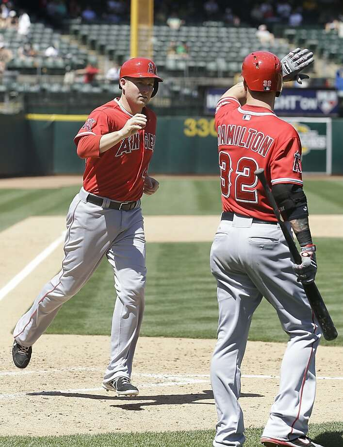 Los Angeles Angels' Mark Trumbo, left, celebrates with Josh Hamilton (32) after hitting a solo home run off of Oakland Athletics pitcher Tommy Milone during the sixth inning of a baseball game in Oakland, Calif., Wednesday, May 1, 2013. (AP Photo/Jeff Chiu) Photo: Jeff Chiu, Associated Press