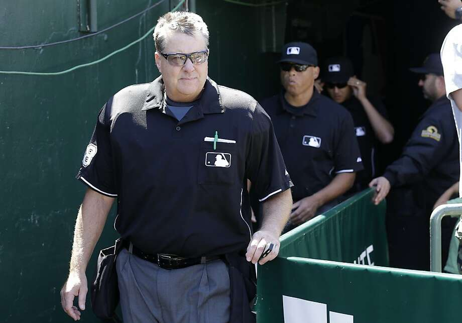 Umpire Gary Cederstrom, foreground, and umpire crew return to the field after reviewing a home run by Los Angeles Angels' Mark Trumbo during the sixth inning of a baseball game against the Oakland Athletics in Oakland, Calif., Wednesday, May 1, 2013. (AP Photo/Jeff Chiu) Photo: Jeff Chiu, Associated Press