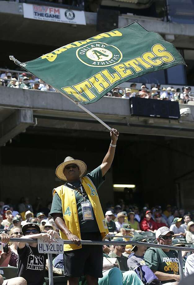 An Oakland Athletics fan waves a flag during a baseball game between the Oakland Athletics and the Los Angeles Angels in Oakland, Calif., Wednesday, May 1, 2013. (AP Photo/Jeff Chiu) Photo: Jeff Chiu, Associated Press