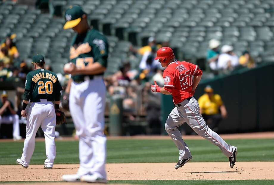 OAKLAND, CA - MAY 01:  Mike Trout #27 of the Los Angeles Angels of Anaheim trots around the bases after hitting a solo home run as pitcher Tommy Milone #57 of the Oakland Athletics looks over a new ball in the six inning at O.co Coliseum on May 1, 2013 in Oakland, California.  (Photo by Thearon W. Henderson/Getty Images) Photo: Thearon W. Henderson, Getty Images