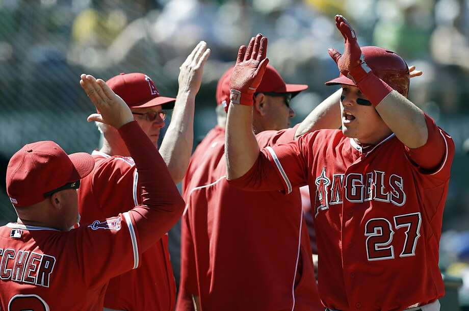 Los Angeles Angels' Mike Trout (27) celebrates after scoring on a sacrifice by Albert Pujols during the eighth inning of a baseball game against the Oakland Athletics in Oakland, Calif., Wednesday, May 1, 2013. (AP Photo/Jeff Chiu) Photo: Jeff Chiu, Associated Press