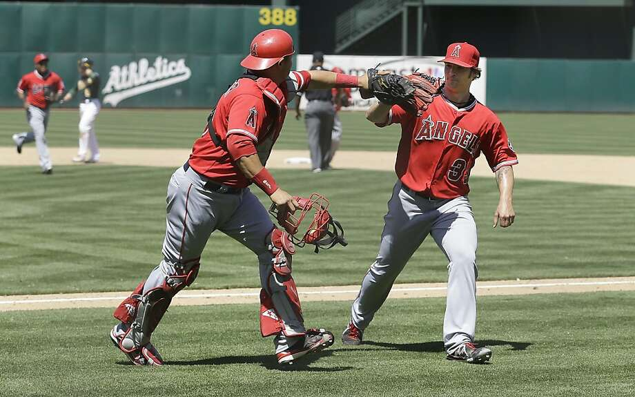 Los Angeles Angels pitcher C.J. Wilson (33) celebrates with catcher Hank Conger (16) after Oakland Athletics' Derek Norris hit into a double play to end the sixth inning  of a baseball game in Oakland, Calif., Wednesday, May 1, 2013. (AP Photo/Jeff Chiu) Photo: Jeff Chiu, Associated Press