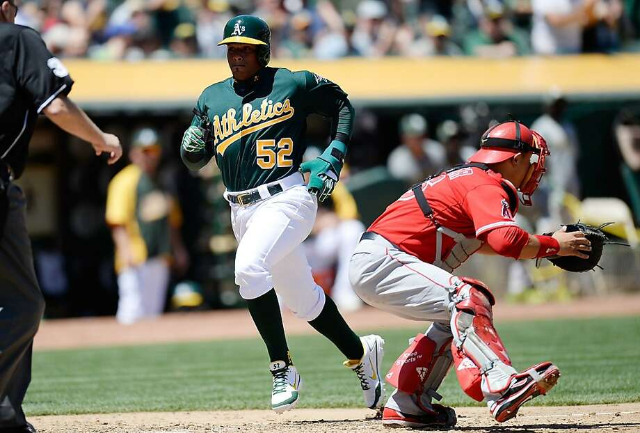 OAKLAND, CA - MAY 01:  Yoenis Cespedes #52 of the Oakland Athletics scores on a Josh Donaldson #20 (not pictured) RBI double against the Los Angeles Angels of Anaheim in the third inning at O.co Coliseum on May 1, 2013 in Oakland, California.  (Photo by Thearon W. Henderson/Getty Images) Photo: Thearon W. Henderson, Getty Images
