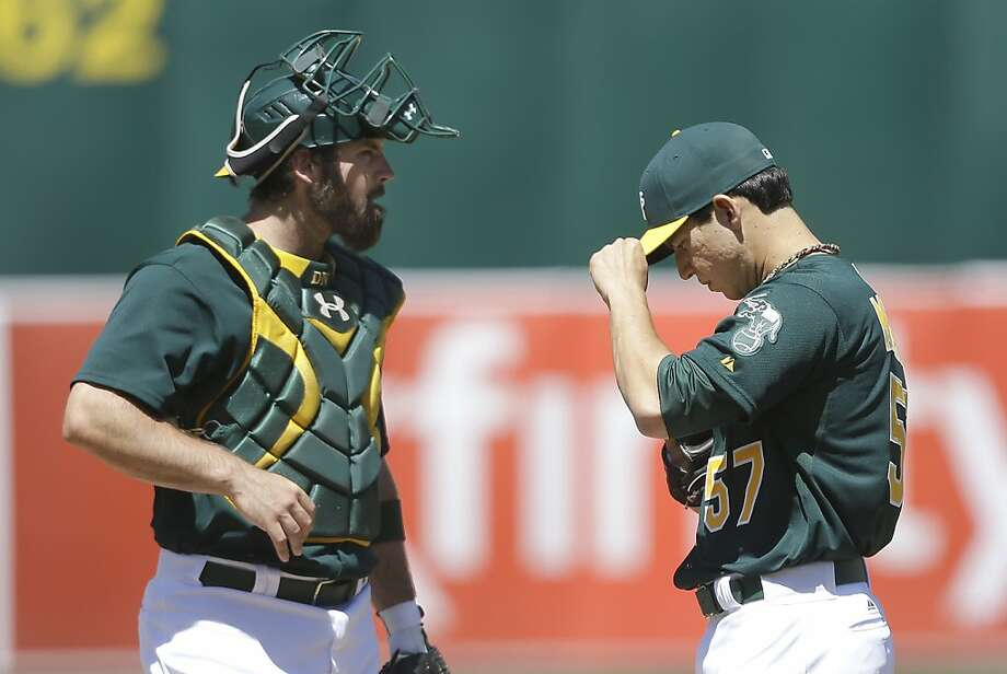 Oakland Athletics pitcher Tommy Milone (57) stands on the mound with catcher Derek Norris as umpires review a home run hit by Los Angeles Angels' Mark Trumbo during the sixth inning of a baseball game in Oakland, Calif., Wednesday, May 1, 2013. (AP Photo/Jeff Chiu) Photo: Jeff Chiu, Associated Press